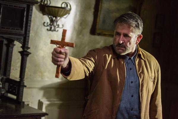 Samuel Mullins versucht es mit dem Kruzifix (Foto: Warner Bros.)